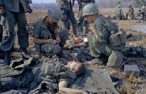In this April 2, 1967 photo, wounded U.S. soldiers are treated on a battle field in Vietnam. (AP Photo/Horst Faas)