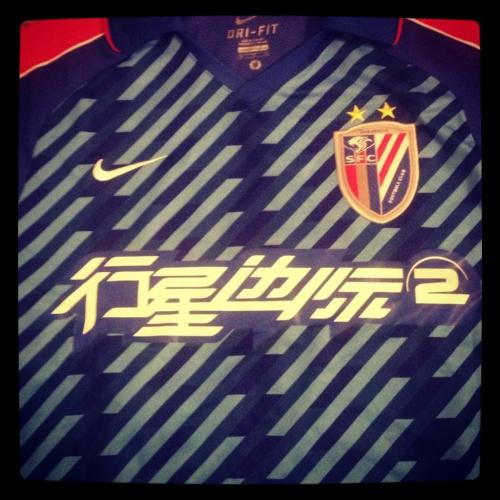 Shirt of the day:  Shanghai Shenhua, Nike, 2012/13 (DROGBA) courtesy of @Benjilanyado Our first Chinese entry into the Football Shirt Collective is a whopper.   Red sleeves with a blue base and lots of diagonal lines.  Magnificent stuff.   Drogba has not made a bad start to his career in China, carrying on from where he left off at Chelsea, bullying defenders into submission with 8 goals in 11 games. Yet despite the big Ivorian's best efforts this was not enough to rescue Shanghai Shenhua from mid-table obscurity, finishing 9th in the league of 16.   Disappointing on the pitch.  Sensational off it.   You can order the shirt here Got a shirt to share on the Football Shirt Collective?  Well it is easy; send us a link to them on twitter or use the #myfavouritefootballshirt # tag, upload them to our facebook page, or pin them on our Pinterest board - and we will publish the best in the collective.