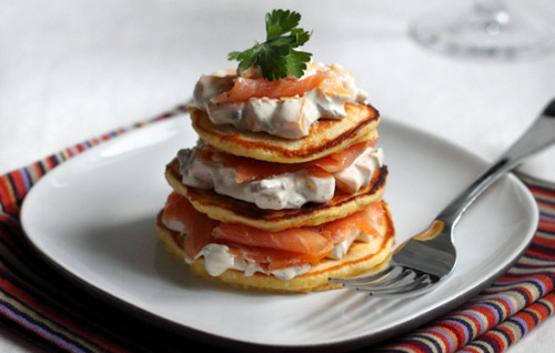 Smoked Salmon and Mango Jalapeno Cream on Cornmeal Blinis 24 paper-thin slices of smoked salmon, the oilier the betterCilantro leaves for garnish For the blinis½ C medium-grind yellow cornmeal½ C all-purpose flour1 scant tsp. baking powder½ tsp. salt2 tbsp. honey1 large egg, beaten½ C plus 2 tbsp. milk1 tbsp. melted butterbutter for frying For the cream1 C crème fraîche or sour creamthe finely diced flesh of a truly ripe mango1 jalapeño pepper, roasted, skinned, seeded and finely diced2 tbsp. finely diced red onionsalt and pepper NOTES: The blinis start drying out instantly, so make them right before serving, if you can. Also, don't let the batter sit – the baking powder makes it rise, and you don't want the blinis to be too spongy. You can replace the jalapeño with any other kind of pepper you like. Replacing the cilantro with a dab of caviar or fish roe takes this nicely over the top. 1. Combine the ingredients for the mango-jalapeño cream in a small bowl and refrigerate for at least 30 minutes. 2. In a medium bowl, combine the cornmeal, flour, baking powder, salt, and honey. In a separate bowl, whisk together the egg, milk, and melted butter. Add the dry ingredients to the wet, and mix until just combined. 3. Heat a large non-stick sauté pan over high heat, and melt a little butter in it. Working in batches, drop the batter by spoonfuls to make 3-inch pancakes. Cook until light brown, 1 to 2 minutes per side. (They're ready to flip when the little bubbles that form on the top start opening.) 4. Assemble three layers of blini-cream-salmon, with a final dab of cream on top, and garnish with cilantro.