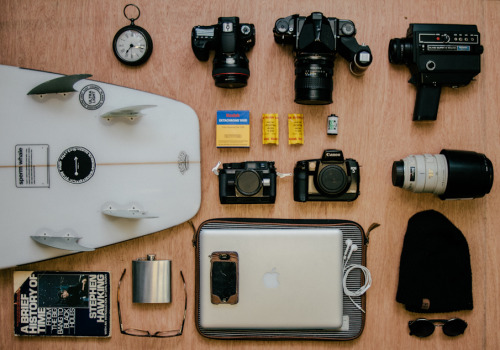 "andrewschoener:  Knolling 1. Extra Large Pocket Watch 2. Canon 7D w/50mm 1.2L 3.Pentax 67 w/75mm f/4 4.Elmo Super 8mm 5.Channel Islands Sperm Whale 5'11"" (with FNA Sticker) 6.Kodak Ektachrome super 8mm film 7.Kodak Portra 400 (2 rolls) 8.Illford HP5 9.Nikonos 3 10. Canon EOS 5 35mm 11. 100-400mmL 12.""A Brief History Of TIme"" by Steven Hawking 13.Flask 14. Glasses 15.Apple Macbook Pro with iPhone 4 w/headphones 16.Beanie 17. Groovy Shades"