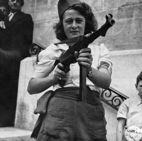 "Seventeen-year-old Simone Segouin, the French partisan known by her nom de guerre ""Nicole Minet,"" with her German submachine gun MP40. Throughout the war and occupation of France she was an active resistance member in the Francs-Tireurs et Partisans group and killed an unknown (but presumably high) number of Germans and was witnessed by American journalists and soldiers to have captured 25 POWs during the fall of Chartres. After the liberation of Paris in August 1944 she was promoted to lieutenant and awarded the Croix de guerre. Read the LIFE article about her, The Girl Partisan of Chartres."