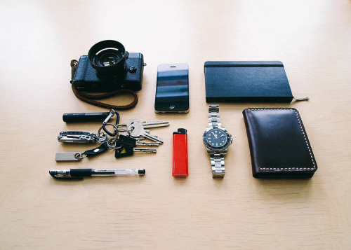 submitted by lillesiim  Hi. Here's my first EDC photo. Fuji X10 with Gordys strap iPhone 4 Moleskine notebook Shkira horween wallet Sterile submariner homage Fenix LD01 Leatherman Style CS Kingston SE9 usb stick Uniball Signo Keys, lighter etc  Editor's Note: Hey there! You've got a pretty sleek carry that looks great for urban use. I noticed your keychain setup could probably benefit from a few small tweaks here and there, especially considering that's where you've designated your light and tools. Consider swapping out that dinky carabiner and consolidate some of your split rings (i.e. one ring for tools, one for keys) to reduce bulk, noise and the risk of rings/clips failing. You can still keep your chain modular but without most of the bulk. Alternatively, you can try suspending and tucking your keys into your pocket, while leaving your tools riding on a belt clip of some sort for quicker access if you need your light or knife in a pinch. I recommend the Lucky Line 40401, here's an example of how I did it. Otherwise, everything looks great! I hope this helps, and thanks so much for sharing.