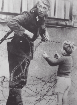 "luminocity:  helenxlove:  lmprovident:  An East German soldier helping a boy cross the newly formed 'Berlin Wall,' 1961. From what is known, the photograph was taken the day the emerging Wall was put up in August 1961 and the boy was found on the opposite side of the wall from his family. Despite given orders by the East German government to let no one pass, the soldier helped the boy through the barbwire. Near the exact time this photo was taken, it was said that the soldier was seen by his superior officer who immediately detached the soldier from his unit. Concerning the fate of the soldier, most descriptions that come with photograph say that ""no one knows what became of him.""  powerful  that german soldier could get it"