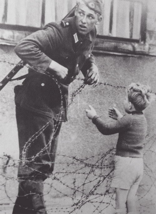 "demons:   An East German soldier helping a boy cross the newly formed 'Berlin Wall,' 1961.  From what is known, the photograph was taken the day the emerging Wall was put up in August 1961 and the boy was found on the opposite side of the wall from his family. Despite given orders by the East German government to let no one pass, the soldier helped the boy through the barbwire. Near the exact time this photo was taken, it was said that the soldier was seen by his superior officer who immediately detached the soldier from his unit. Concerning the fate of the soldier, most descriptions that come with photograph say that ""no one knows what became of him."""