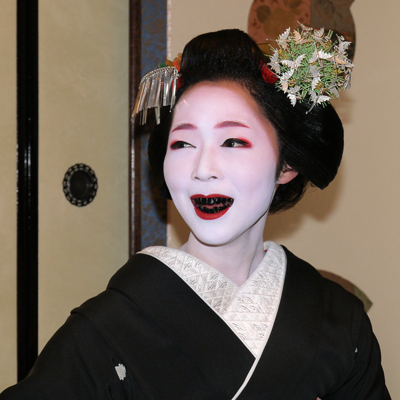 The process of ohaguro - permanently dyeing one's teeth black with lacquer. The darkness in the mouth makes the face look more like a mask.