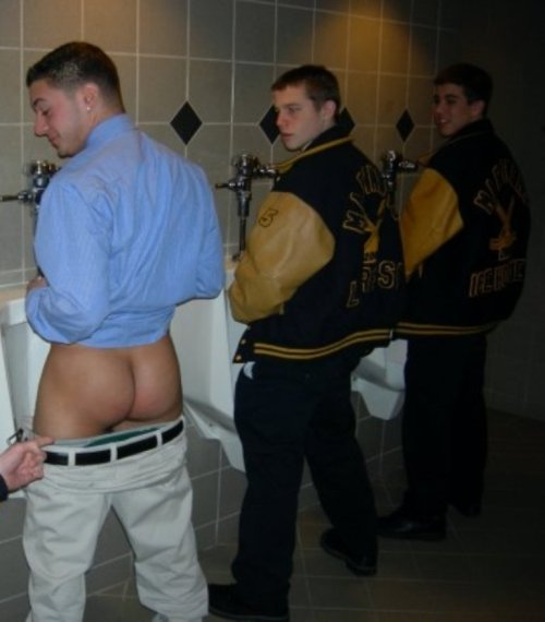 Three teammates pissing at the urinals