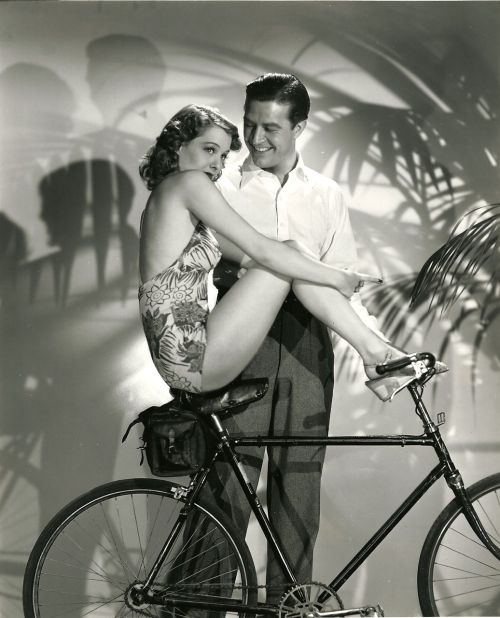 Ellen Drew rides a bike. Ray Milland lends a hand, and a smile.
