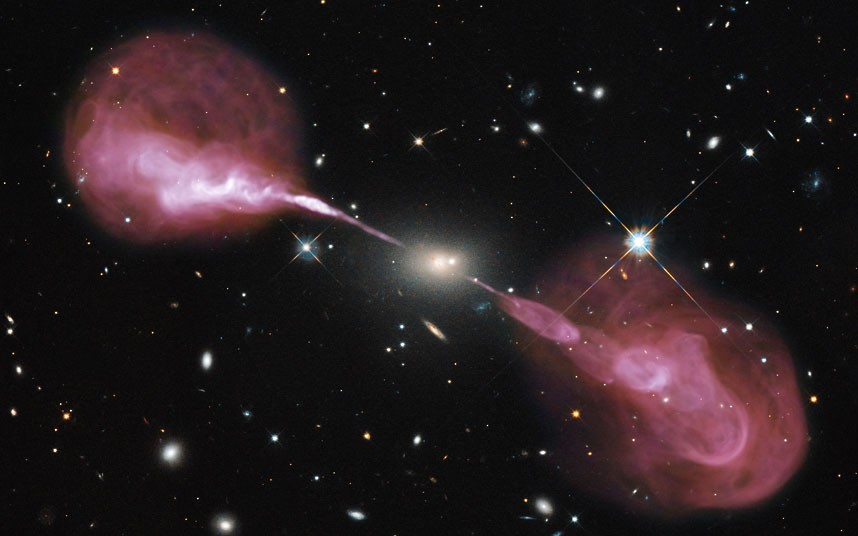 Jets powered by the gravitational energy of a super massive black hole in the core of the elliptical galaxy Hercules A are seen in this composite image from the Hubble Space Telescope's Wide Field Camera 3 and the recently upgraded Karl G. Jansky Very Large Array (VLA) radio telescope in New Mexico. Hercules A is some two billion light-years away and is roughly 1,000 times more massive than the Milky Way; the black hole at its center is 2.5 billion times the mass of our Sun. (Photo: NASA / ESA via Rex Features/ The Telegraph) Whoa.