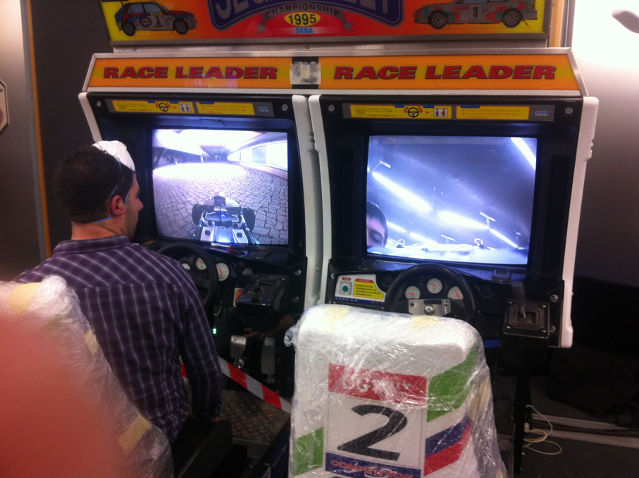 Arcade Machine Hacked To Control RC Cars Take a close look at the Sega Rally arcade cabinet pictured up top. Those aren't the game's graphics on the screen. It's a live feed from a camera mounted onto an RC car that it controlled by the arcade. There's even an option to switch between 1st and 3rd person views!  The cabinet is hooked up to an Arduino and I'm sure there's all sorts of sciency stuff involved that I won't ever understand, but it's all pretty dang fresh. The whole project was developed for the SAPO Codebits VI conference in Portugal. Check out some footage of the Sega Rally Championship RC Cars Project below.