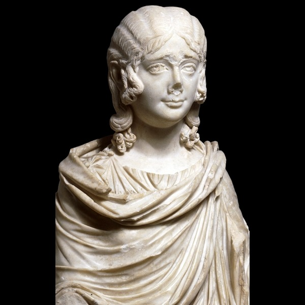ancientpeoples:  Marble bust of a girl Roman, made in Italy about AD 210-230 The girl is shown dressed in a Greek-style chitoncovered by a cloak. Perhaps the most striking feature is her hair, or rather the cap-like wig with its central parting and waved sides, underneath which the long tresses of her own hair can be seen. This type of mid-length portrait, extending to the waist, is characteristic of the early to mid-third century AD. Wealthy women lavished a great deal of care and attention on their hairstyles, keeping a servant known as an ornatrix specifically for the purpose. A century or so before this portrait was made, during the reign of the emperor Trajan, women's hair reached almost literally dizzying heights. Hairpieces and frames were used to create hairstyles involving great banks of curls. The satirist Juvenal observing a well-known lady of the time noted the '….numerous tiers and storeys on her head.', but adds, drily, 'She is not so tall behind, you would not think it was the same person.' Real hair was used to make these hairpieces and other wigs; dark hair was imported from as far afield as India, while a bleach made of beech ash and goat's fat was used to turn hair blond. The exchange of peoples and ideas throughout the Roman Empire ensured that female (and male) hairstyles were almost as influenced by changes in taste and fashion as they are in modern times. In particular the hairstyles of members of the imperial family, seen on statues and coins, were faithfully reproduced. Perhaps the greatest revolution in men's hair fashions came with the emperor Hadrian (AD 117-138). He adopted the beard and moustache, popular in the Greek eastern Mediterranean, and made facial hair acceptable and fashionable for men in the Latin west for the next century. (Source: The British Museum)