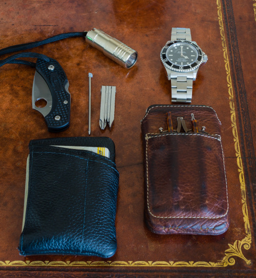 submitted by shelt  Love your blog!  Here's my EDC, after many generations… Bladeart Mission Wallet containing: - Spyderco Dragonfly2- Swisscard Pen- Swisstech 4-in-1 screwdriver- cards & cash  iPhone 4s in Ikonic Edge case (with eBay folding reading glasses)Lummi Raw NS 250/40 Lumen with green tritiumRolex Submarinersmall keyring with house and car key - not shown   Editor's Note: Thanks for the love! Your carry looks to be well organized — good use of those multipurpose pouches for your gear. It's always interesting to see those urban wallets and how people set theirs up. I also wanted to highlight that awesome Lummi light and how the Dfly is a good EDC blade. I see you want to keep your pen as barebones as possible (as do I), but for something a little sturdier and more comfortable (but still very compact) take a look at the Pilot Birdy Mini SS. I reviewed it here. Otherwise nice setup, thanks for sharing!