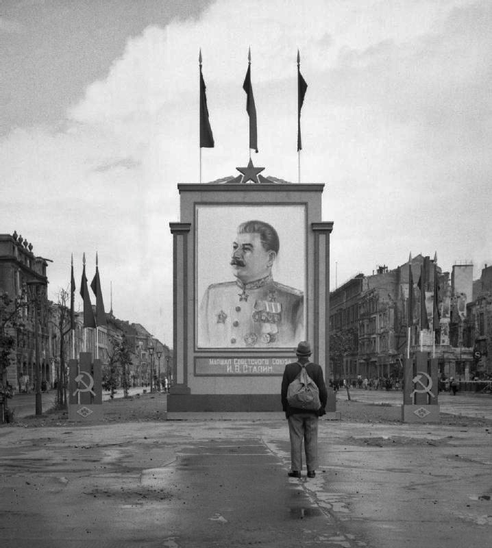 collectivehistory:  A German civilian looks at a large poster portrait of Stalin on the Unter-den-Linden in Berlin, 3 June 1945.