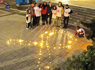 This photo was taken during a World AIDS Day observance in Lovech, Bulgaria in 2011. Youth volunteers from the Bulgarian Red Cross spent the afternoon passing out brochures, condoms, etc. in the Lovech city center. The event culminated with the lighting of an AIDS awareness ribbon. - Peace Corps Health Volunteer Horace Askins