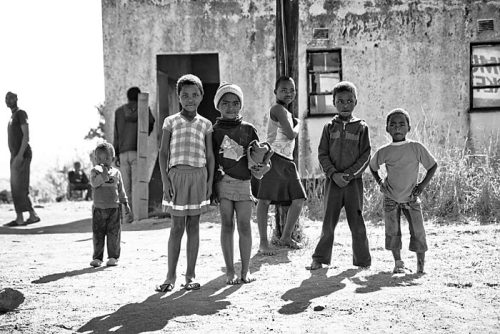 One in Four Children stand in front of a local store in a mountainous region of Swaziland—the country with the highest HIV rate in the world. One in every four people is infected with the virus, while everyone in this small country is affected. The children of Swaziland suffer the most, many losing their parents to the epidemic. But the children are also the future, empowered with knowledge and hope that the HIV epidemic can be conquered. According to statistics, it is likely that at least one of the children in the photo has HIV. Taken by Peace Corps Volunteer Ryan Fouss