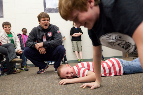 Kaden Powers (center), 12, collapses on his 35th pushup alongside fellow classmate and competitor Thomas Allen (right), 13, during a contest put on by Olympic wrestler Jake Herbert (left) as he shouted words of encouragement at Grand Blanc West Middle School in Grand Blanc, Mich. on Tuesday, November 27, 2012.