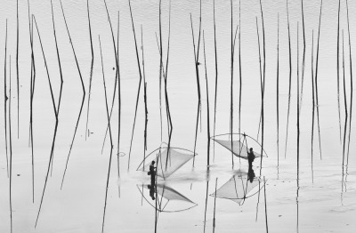 Two Fisherman by Peng Jiang - The shoal is one of the most fascinating places in Xiapu, China. Fishermen farm fish, shrimp, and oysters and plant seaweed along this coast area.