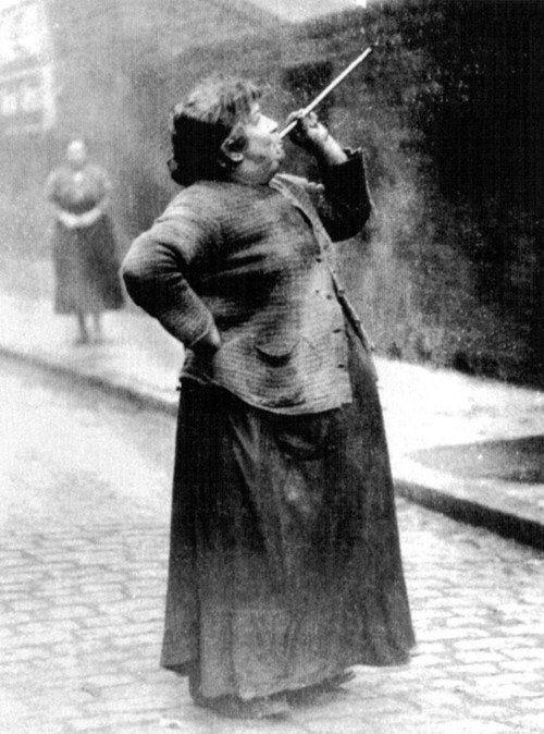 notcuddles:  collective-history:  Mary Smith earned sixpence a week shooting dried peas at sleeping workers windows. A Knocker-up (sometimes known as a knocker-upper) was a profession in England and Ireland that started during and lasted well into the Industrial Revolution and at least as late as the 1920s, before alarm clocks were affordable or reliable. A knocker-up's job was to rouse sleeping people so they could get to work on time. The knocker-up used a truncheon or short, heavy stick to knock on the clients' doors or a long and light stick, often made of bamboo, to reach windows on higher floors. Some of them used pea-shooters. In return, the knocker-up would be paid a few pence a week. The knocker-up would not leave a client's window until sure that the client had been awoken. There were large numbers of people carrying out the job, especially in larger industrial towns such as Manchester. Generally the job was carried out by elderly men and women but sometimes police constables supplemented their pay by performing the task during early morning patrols. Photograph from Philip Davies' Lost London: 1870 - 1945.  I am delighted by this.