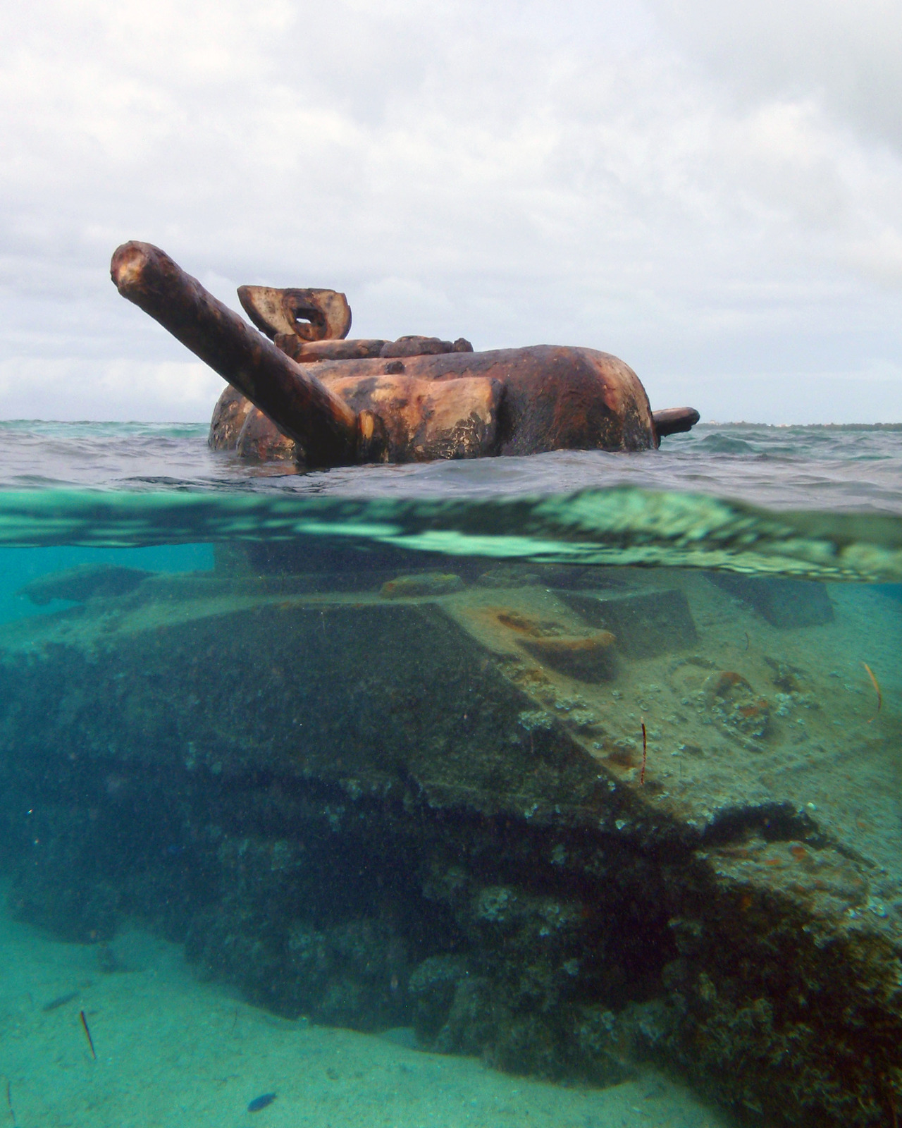 wolife:  This US M4 Sherman Tank was stranded on the reef during the invasion of the island of Saipan during WWII. Its turret is still frozen in time, taking aim at a Japanese gun emplacement on the beach. G spotted this in the surf while we were on the way to the airport and we just HAD to swim out to it.  Being able to take this photograph made for the GREATEST 30th birthday present.