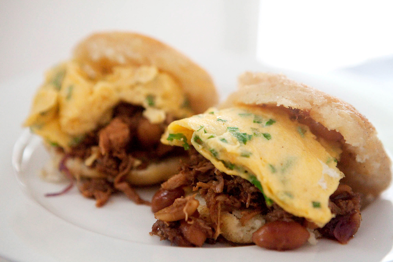 "Pulled Pork and Scrambled Egg Arepas Every now and then I see an idea and think, ""why didn't I think of that?"".  Such is the case with Sydney start-up Hungry Mondays, who slow-cooks food all weekend for Monday delivery, in vacuum sealed bags that stay fresh for 10 days.  Now, while I think my barbeque pulled pork is better as I prefer a different style of barbeque (I am not-so-subtly petitioning to guest chef), I had some leftovers from the massive portion I attempted to eat for a late night snack the night before that I used to make breakfast the next morning.  Chop some herbs and scramble the eggs, and you can use my standard arepa recipe to fill with leftover pork and the eggs.  This one's a hangover cure."