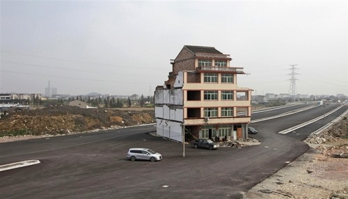 China tears down house in middle of highway after owner agrees to demolition (Photo: China Daily / Reuters) Authorities have demolished a five-story home that stood incongruously in the middle of a new main road and had become the latest symbol of resistance by Chinese homeowners against officials accused of offering unfair compensation. Read the complete story.