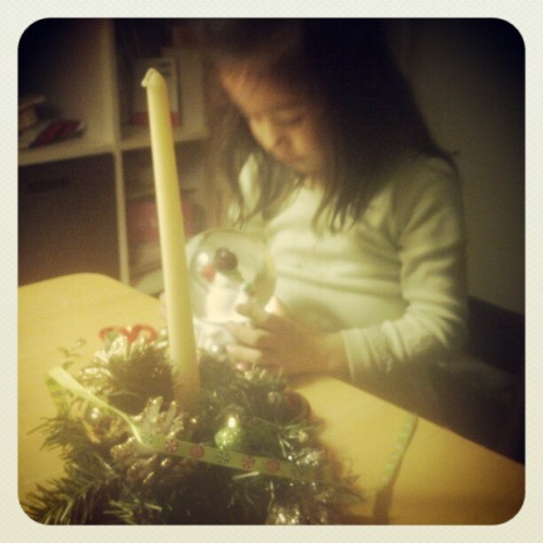 Julia playing with a snow globe. She decorated this beautiful candle.