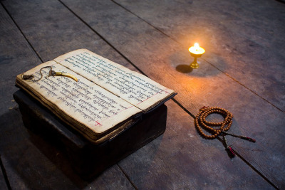 kelledia:   Pecha (prayer book), mala and candlelight. Langtang area, Nepal.