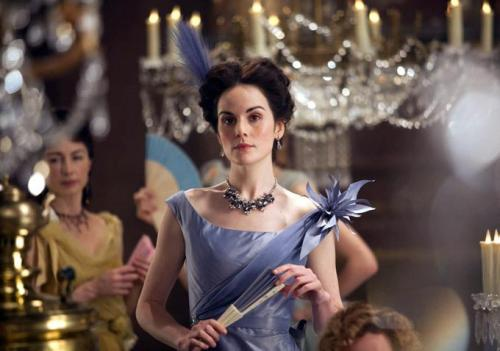 Anna Karenina - Michelle Dockery as Princess Myagkaya wearing an off-shoulder lavender taffeta gown with draped corset and floral decoration on one shoulder.