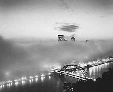 "1990: ""Fog on the City""  This image by the late Clyde Hare, taken in 1990, captures a fog-shrounded Pittsburgh although the Fort Pitt Bridge, the USX Tower and the spires of PPG Place are visible.  Mr. Hare grew up in the gently rolling hills of southern Indiana and moved to Pittsburgh in 1950 to work with Roy E. Stryker, the father of photojournalism.  He worked on the Pittsburgh Photographic Library Project, covering the city's first renaissance from 1950 to 1953. He was friendly, good-humored and intelligent.  Mr. Hare, whose nickname was ""Red,"" captured Pittsburgh's gritty industries in black and white splendor. He also used color images to chronicle subsequent urban renaissances forged by corporate and civic leaders. Sometimes, he used an unusual Linhof 4x5 inch film view camera.  Mr. Hare, who died in 2009, was a freelance photographer for more than 50 years in Western Pennsylvania. U.S. Steel, Westinghouse and Heinz were among his clients.  His book, ""Clyde Hare's Pittsburgh,"" is a visual ode to the city that captured his imagination.   (Photo by Clyde Hare, Post-Gazette) — Marylynne Pitz"