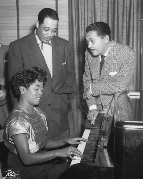 "Sarah Vaughan plays the piano as Duke Ellington and Billy Eckstine look on, circa 1950. The Newark, NJ-born Ms. Vaughan studied piano as a child and went on to win first prize at the Apollo Theater's famous Amateur Night competition. Billy Eckstine was in the audience that night and before long, Ms. Vaughan would sing with Mr. Eckstine in his band. Her recording of ""The Duke Ellington Songbook, Vol. 1 and 2,"" is still unmatched for its beauty and brilliance. Photo by Gilles Petard/Redferns."