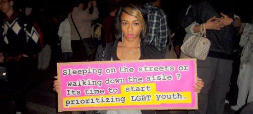 "[Image: A Black woman holding a pink sign that says, ""Sleeping on the streets or walking down the aisle? It's time to start prioritizing LGBT youth.""] I saw this floating around facebook today. Credit where credit is due."