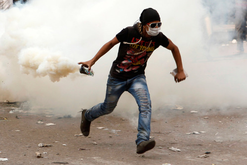 simply-war:  A protester runs to throw a tear gas canister back at police during clashes near Tahrir Square in Cairo, as anti-Morsi protesters start to gather in the square on Nov. 27. (Asmaa Waguih/Reuters)