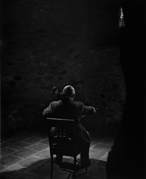 "theantidote:  Yousuf Karsh: Pablo Casals, 1954 In the Abbey de Cuxa in Prades, I spent several glorious hours with the master of the cello. Our rapport was instantaneous - he trusted me to carry his cherished instrument. I was so moved on listening to him play Bach that I could not, for some moments, attend to photography. I have never photographed anyone, before or since, with his back turned to the camera, but it seemed to me just right. For me, the bare room conveys the loneliness of the artist, at the pinnacle of his art, and also the loneliness of exile.Years later, when this portrait was on exhibit at the Museum of Fine Arts, Boston, I was told that an elderly gentleman would come and stand in front of it for many minutes each day. When the curator, by this time full of curiosity, ventured to inquire gingerly, ""Sir, why do you stand day after day in front of this portrait?"" he was met with a withering glance and the admonition, ""Hush, young man, hush - can't you see, I am listening to the music!"" (via onlyoldphotography:)"