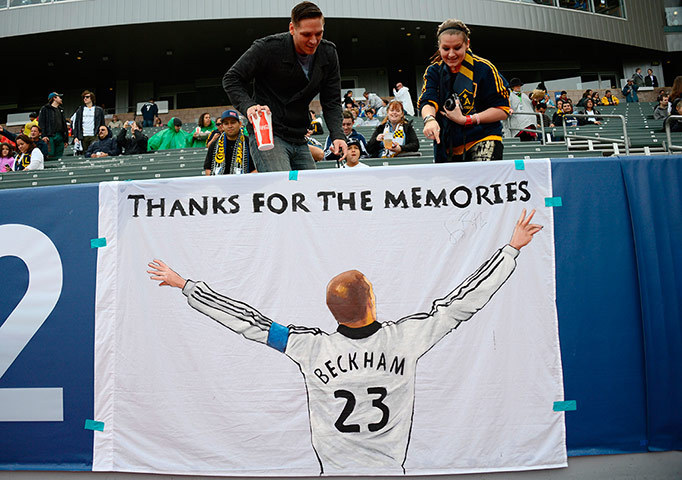 VICTORIOUS BECKHAM  Fans stand above a poster paying tribute to David Beckham before the MLS Cup in Los Angeles on Saturday.  Beckham and the LA Galaxy defeated the Houston Dynamo, 3-1, for the team's second consecutive championship; this is Beckham's final season with the team he joined five years ago.  (Photo: Robyn Beck / AFP-Getty via The Guardian)