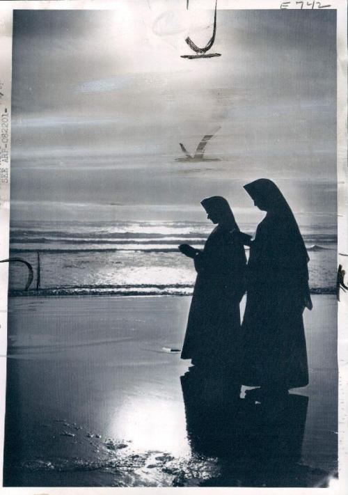 """Praying Nuns are silhouetted against the setting sun streaking across the Pacific at Grayland, Wash. The sisters belong to the order of St. Benedict, St. Placid Priory, Olympia Wash. The Prioress Rev. Mother Placidia, arranged for the sisters to vacation at the ocean side; she said: """"People need to enjoy nature every so often to be able to do their best, whatever it may be."""" …Wire Photo dated August 24th, 1960."""