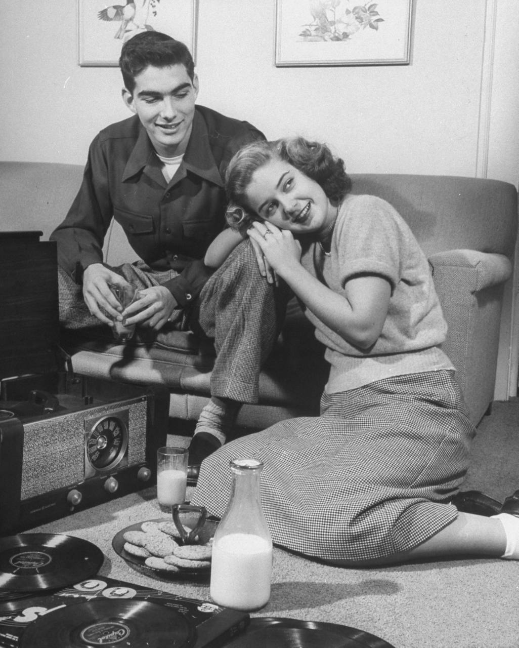 Teens, 1948 This teenage couple is listening to records and having a snack of milk and cookies.