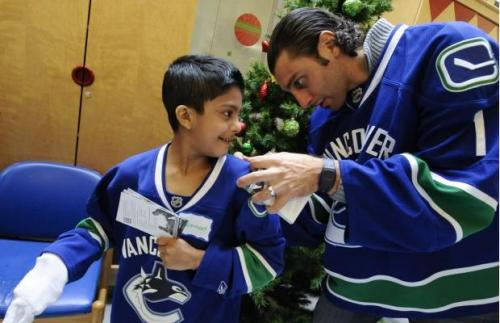 hockeyplayerswithchildren:  Roberto Luongo embracing the Christmas spirit and signing this kid's jersey.