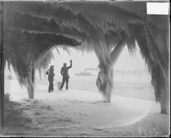 Two men standing near iced-covered water intake cribs, and staring at a steamer boat in the distance. Chicago, 1929. Photograph by Chicago Daily News, Inc. Want a copy of this photo?  > Visit our Rights and Reproductions Department and give them this number: DN-0090257 Connect with the Museum
