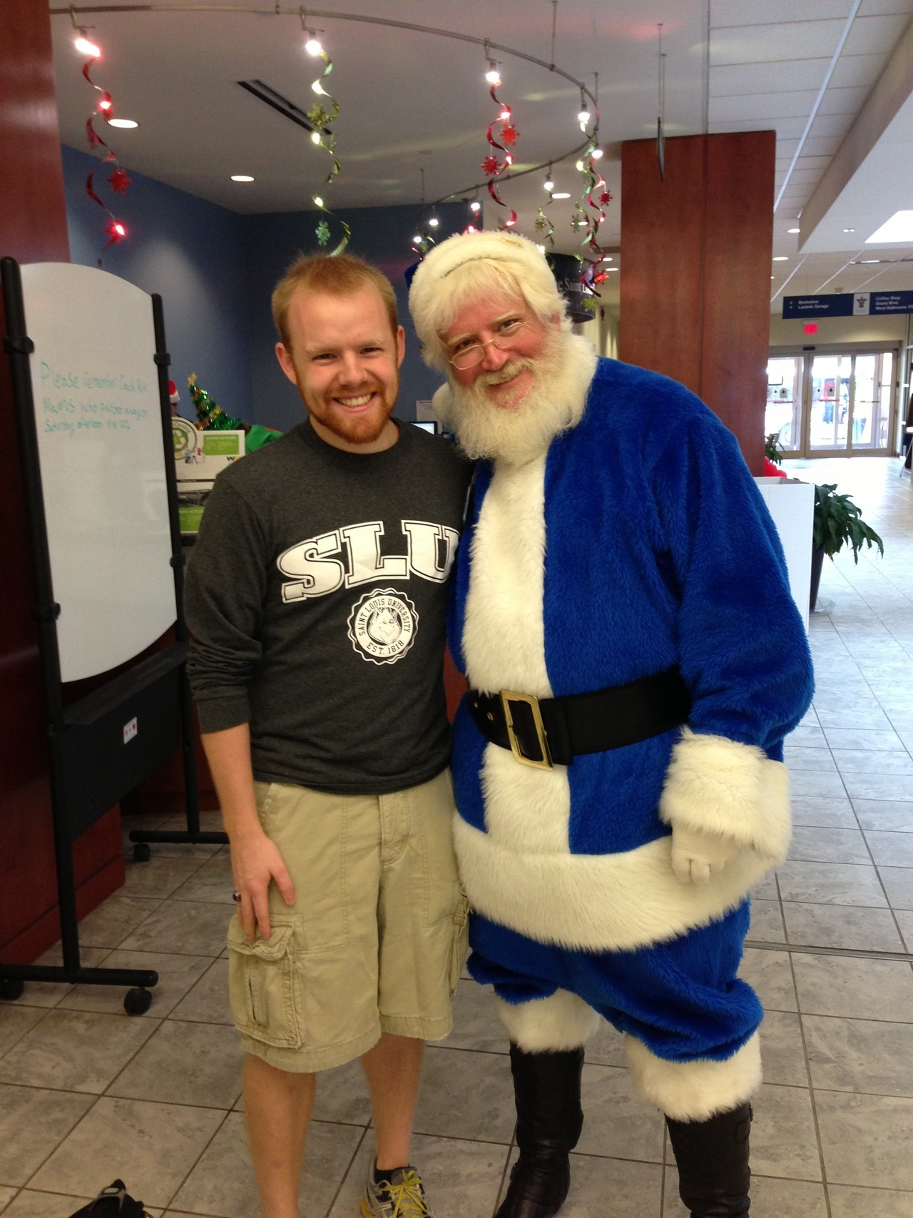 "The Blue Santa Saint Louis University has many Christmas traditions. From the annual Christmas tree lighting in Samuel Cupples House, to the garland, wreathes and holiday lights strung around campus, to the red bows hung on every lamp post, SLU is decorated and ready for the season! Minus the 70 degree weather we had this weekend (which was amazing and most welcome!) it's beginning to feel a lot like Christmas around here! As I was walking through the Busch Student Center this morning I came across a very special visitor - The Blue Santa! After snagging a picture with him, I knew I had to share with y'all what exactly The Blue Santa is and why he's such a big deal here at SLU. Every December The Blue Santa goes to all the faculty and staff offices at Saint Louis University and collects new, donated toys. This coming Thursday, local inner-city kids who may come from more impoverished families will be invited to SLU for a big Christmas party, where Santa will give them each one of the donated toys. This year The Blue Santa has already collected 2,000 toys! All toys leftover from the big St. Nick's Day party on Thursday will then be donated to local shelters, schools and non-profits that also assist families during the holiday season.  In case you were wondering what it means to be a ""Jesuit"" institution… This is one of the best examples as to how our mission here at SLU is lived out daily. Generosity. Saint Louis University. Always in the spirit of giving. AMDG"