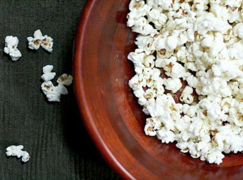 "jinifit:  Popcorn: Yes,You Can Still Eat It     With all the fear (duly warranted) surrounding GMO foods, there is growing hesitation out there about eating that favorite of comfort foods: popcorn.  Well that's just…anti-American.  But corn is the most common GMO food known to man-and it's in everything.  So while many of us will eschew our old childhood friend, even at the movies-in order to avoid eating Frankenfood, others like me, will create their own brand of ""Smartpop."" If you're old enough to remember the days of stove-top Jiffy Pop where your Dad (or Mom) would swirl that coiled foil package with the wire handle endlessly over the burner flame while you waited at their elbow to watch the foil puff up, slowly at first, listening for that first kernel to pop…and then another…and then a few more, and then all at once, in rapid succession, even more-giving way to a flurry of popping, then you're about to relive your childhood over the stovetop.Making stove-top popcorn is really easy, but first I want to assure you that this recipe uses only certified organic popping corn which by definition, means it is NON-GMO.  Pair it with a healthy fat like coconut oil (with a high flash point that is not prone to oxidation) and all you have to worry about is the ensuing carb orgy.Here's how to make perfect popcorn - crisp, tasty and light, every time.                                                 Stove Top Popcorn2  tablespoons of coconut oil½ cup of Eden brand or 365 brand popcorn- (available at Whole Foods Markets)Sea salt or, vanilla flavored saltHeat coconut oil in a large, heavy saucepan over a medium high flame. Choose a saucepan big enough to hold all the popped corn, (and remember that heavier pans are less prone to burning.)While the oil is heating, add 2 or 3 kernels of popcorn to the oil. When these kernels pop, the oil is now hot enough to add the remaining popcorn. Add the remaining popcorn and quickly cover the pan with a lid (so as not to be burned by hot oil ""spitting"" on you.)  Shake the pot to make sure all the kernels are moving around and are being covered in oil.  Keep the lid just slightly ajar to let the steam being created escape. It will make for lighter, fluffier popcorn.Keep the pan on the heat, shaking almost constantly. The kernels will start rapidly popping. Keep shaking the pot until the popping slows to one every second or two. Remove from the heat and remove the lid as soon as you're sure that popping has really stopped (the lid should face away from when you remove it so as not to get burned by the steam.) Don't wait until every last kernel has popped before removing from heat or you run the risk of burning the popcorn–a few un-popped kernels never hurt anyone.Quickly add the sea salt while the oil is still hot and even glistens on the popcorn, (so that it sticks.)  Toss, and ""pop"" in that great movie you've been waiting to watch on a crisp autumn evening such as this. Follow Jini Cicero a personal trainer with 20 years of experience"