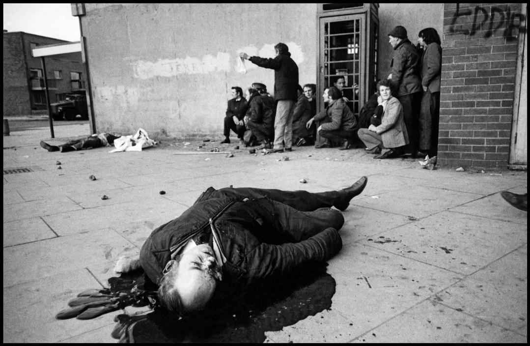 A victim, Barney McGuigan, lies in a pool of blood as the shooting stops on Bloody Sunday, Derry, 1972 by Gilles Peress.