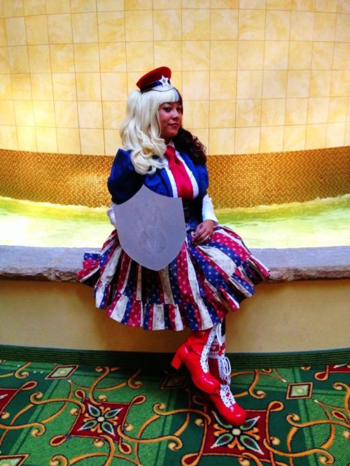 blasphemina:  Me as Lolita Captain America at Teslacon XD It was my first time cosplaying in years and the first time I organized a cosplay group.  So much fun! I have the Double Victory shield and half dark hair as an homage to Isaiah Bradley. Hat: Apatico Vest, Skirt, Jacket: Blasphemina's Closet (Me) Blouse: Offbrand Shoes: Caramel Candy Wig: Gothic Lolita Wigs  Why yes, Lolita gent Coulson IS getting her trading card signed.  Hurray!