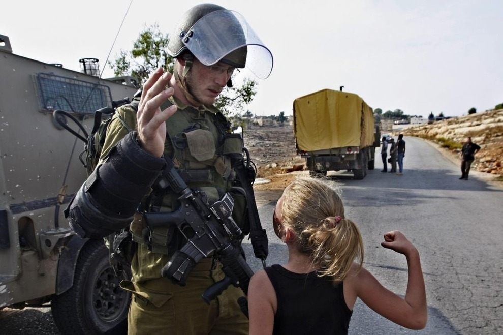 xeb695:  A little Palestinian girl vs. an Israeli soldier A Palestinian girl tries to punch an Israeli soldier during a protest against the expansion of the nearby Jewish settlement of Halamish. Image by Majdi Mohammed / AP