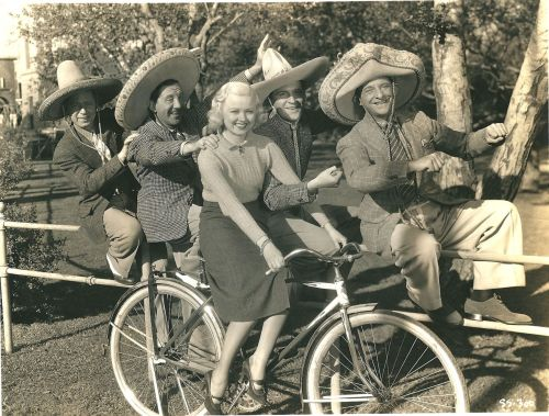 Busby Berkeley blond rides a bike. The Yacht Club Boys ride a fence.