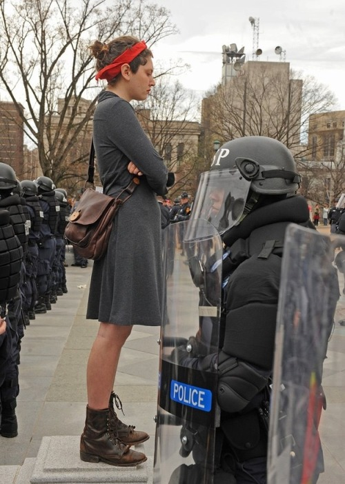 grrrl-riot:  One of my favorite photos from 2012.    Virginia police in full riot gear showed up at a women's rights protest at the Virginia State Capitol this weekend. Hundreds of people were protesting a new amendment that passed that Virginia House that would require women to have an ultrasound before having an abortion. 31 people were arrested.     THIS. IS. SO. POWERFUL. FOR. ME.