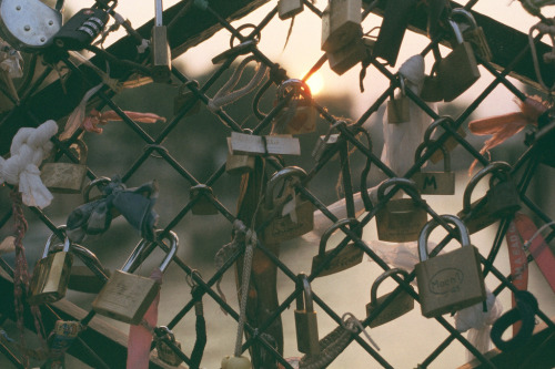 "Paris, France. Couples write their names on ""love locks"" and locks them onto a bridge, then the key is thrown into the Seine River. This symbolizes undying love."
