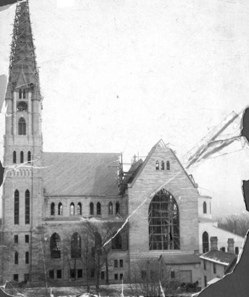 WEST FACADE OF GESU CHURCH (MILWAUKEE) AS IT UNDERGOES CONSTRUCTION (1892) Scaffolding covers the west clock tower and is visible through the west transept window. The main roof over the nave is still being completed and all of the windows are empty. Photographer: Miller & Breitwish http://digitalmarquette.cdmhost.com/cdm/singleitem/collection/p128701coll6/id/233/rec/57 Courtesy Department of Special Collections and University Archives, Marquette University Libraries. MUA_CB_00313