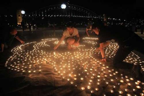 """Volunteers help light a candle mural on the forecourt of the Opera House representing WWF and 60+ before the lights are switched off for Earth Hour. Photo: Getty Images for WWF Australia."" (via Spreading the Earth Hour message)"