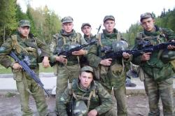 военнослужащий Russian soldiers posing for a photo after (or before) training. They're equipped with the AK-74M, you can see the side-folding stock button on the rear of the receiver. What's interesting here is that all of the rifles have the 1P29 optic. That scope is a copy/clone of the British Trilux SUIT. One major difference is that the 1P29 still incorporates the Dragunov style reticle.