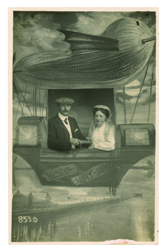 Photo postcard of a Victorian couple sitting in a studio mock-up of a hot-air balloon. Photo by J. E. Ballantyne, from Fantasy Travel: Vintage People on Photo Postcards by Tom Phillips.