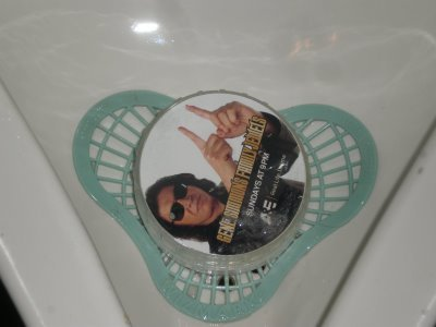 Gene Simmons taunts you, via pantomime, from a urinal cake regarding the size of your family jewels.